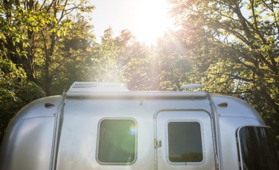 image of small airstream trailer surrounded by trees with sunlight shining through