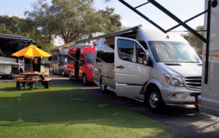 Several RV Vans red and silver with picnic table and yellow umbrella